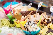image of ice cream sundaes  - Many different sorts of ice in an ice cream parlor for sundaes and cones - JPG