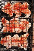 stock photo of charcoal  - fresh raw chicken wings on barbecue grid over charcoal spread with paprika and red hot pepper ready to cooking - JPG