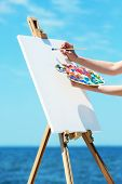 pic of paint palette  - Female hand holding palette with paints and easel with canvas on beach - JPG