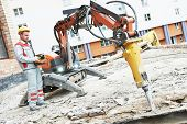 image of millwright  - builder worker in safety protective equipment operating construction demolition machine robot - JPG