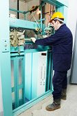 picture of elevator  - male technician machinist worker adjusting elevator mechanism of lift with spanner - JPG