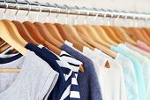 image of clothes hanger  - Different clothes on hangers close up - JPG