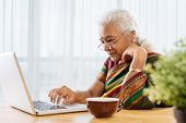 foto of old lady  - Serious old Indian lady working on laptop - JPG