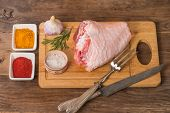 picture of thighs  - Raw turkey thigh with spices on a wooden background - JPG