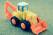 foto of backhoe  - Vintage Style Tractor Backhoe Toy on sand - JPG