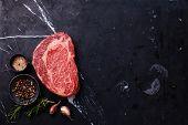foto of ribeye steak  - Raw fresh marbled meat Black Angus Steak Ribeye and seasonings on dark marble background - JPG