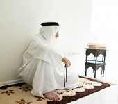 picture of arab man  - Arabic aged man sitting on ground using traditional beads - JPG