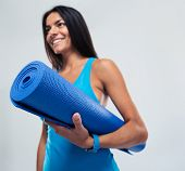 pic of yoga mat  - Smiling fitness woman holding yoga mat over gray background - JPG