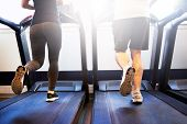 foto of treadmill  - Lower Body Shot of Healthy Athletic Couple Running on Treadmill Machine Inside the Fitness Gym - JPG