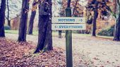 Постер, плакат: Signboard With Two Signs Saying Nothing Everything Pointing In Opposite Directions