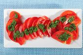 picture of pesto sauce  - Salad of sliced tomatos with pesto sauce close up  - JPG