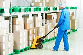 stock photo of forklift  - medical warehouse worker man loading boxes with medcine drugs by hand forklift  - JPG