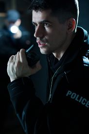 foto of police  - Portrait of a young police officer holding radio - JPG