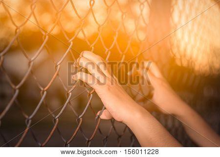 Hand holding on chain link fence on Thailand .