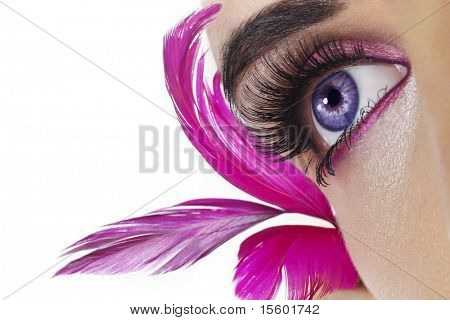 Beautiful woman`s open eye. Pink feathers on background.