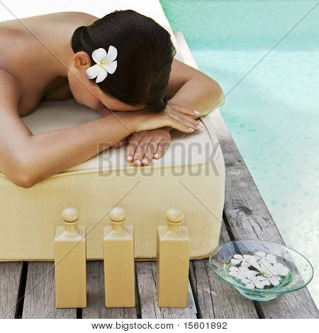 Beautiful woman getting spa treatment near the swimmingpool