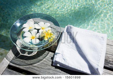 Flores en agua en el piso de madera cerca de la piscina