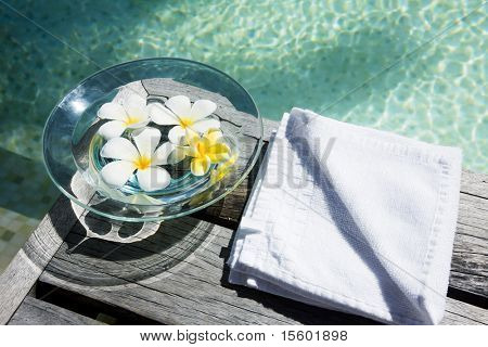 Flowers in water on wooden floor near the swimmingpool