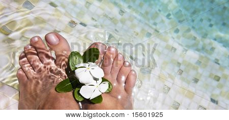 Woman feet in water at swimmingpool. A lot of copy space.