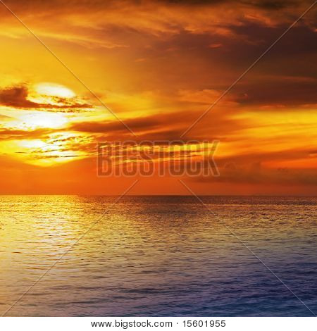 Dramatic sunset sky with clouds over ocean