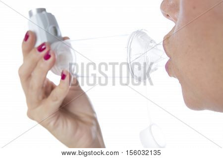Detail of a mouth is inhaling the medicament from the pressurized cartridge inhaler placed on an inhalation chamber - Isolated on a white background