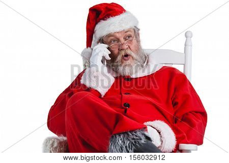 Santa claus talking on mobile phone against white background