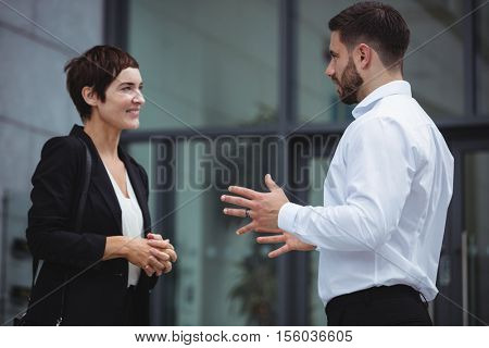 Businesspeople interacting with each other in office premises