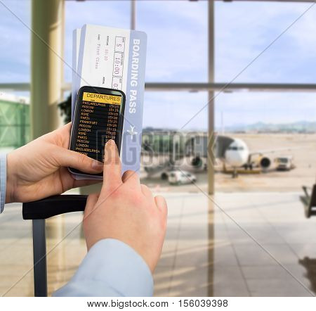 Hand holding mobile smart phone with connect wifi on the airport and see departures board