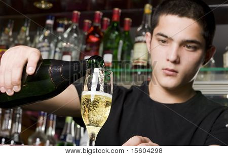 Barman pouring champagne. Focus on glass and bottle