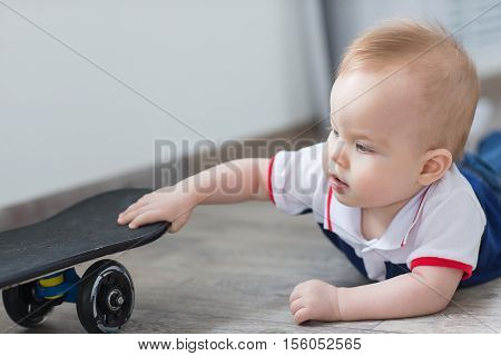 The little boy was crawling on the floor to the skateboard.