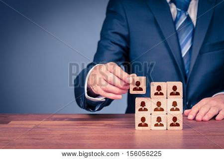 Human resources, social networking, assessment center concept, personal audit or CRM concepts - recruiter complete team by one person. Employees are represented by wooden cubes with icons.