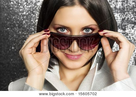 Stylish woman on silver sparkling background