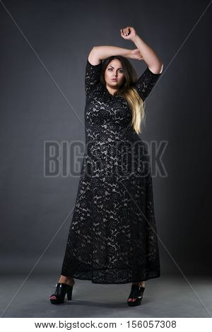 Young beautiful plus size model in black dres xxl woman on gray studio background full length portrait