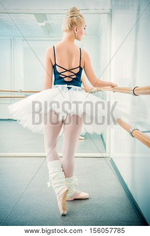 Beautiful ballet dancer training near the ballet barre in a ballet class.