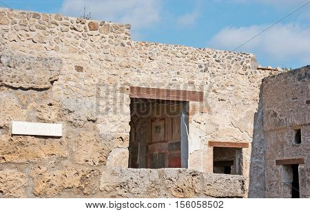 The preserved details of the painted interior of Roman villa through the window in ancient stone wall Pompeii Italy.