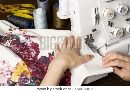 Seamstress sewing on overstitching machine. Sewing items on table.