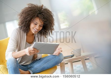 Mixed-race woman websurfing on digital tablet at home