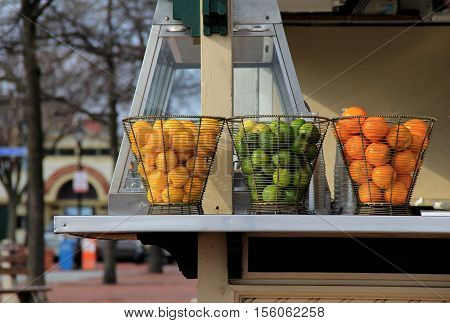 Three wire baskets filled with fresh lemons, limes, and oranges