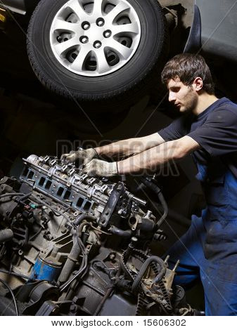 Auto mechanic checking an internal combustion engine