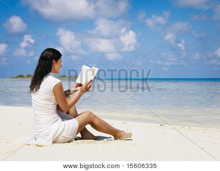 Woman reading book near the ocean