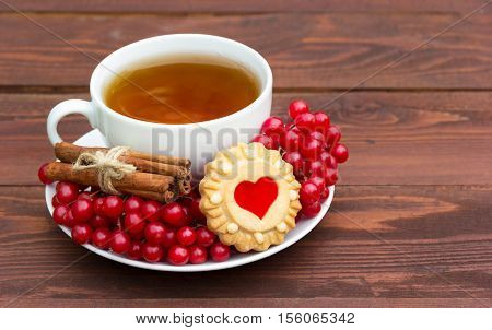 Winter warming tea with cinnamon and berries. Cookies in the shape of a heart. Romantic concept. Black tea in a white cup and red berries. Copy space.
