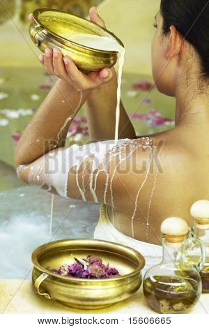 Young woman at spa centre taking milk bath