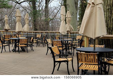 Several tables and chairs with heavy umbrellas set on beautiful wood decking in outdoor area of park.