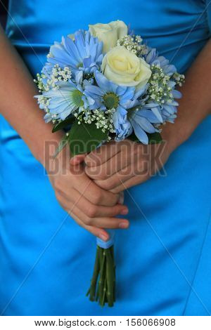Vertical image of young bridesmaid, dressed in blue, holding  wedding bouquet as she gets ready to walk down the aisle to ceremony.