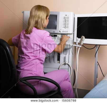 Doctor working on ultrasound equipment at modern clinic.