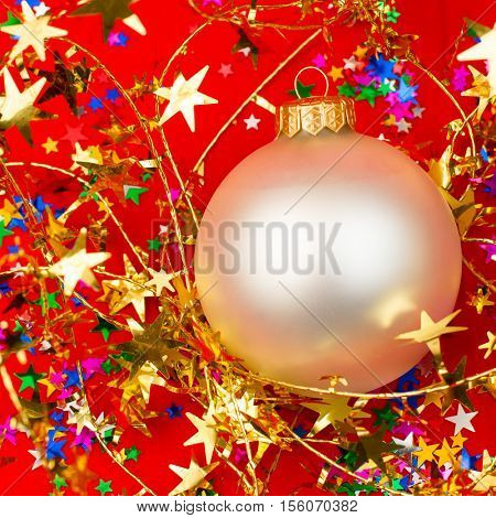 Christmas bauble with tinsel on red background