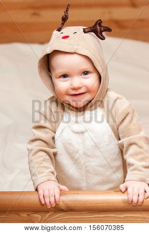 Happy little baby girl wearing deer costume looking at camera smiling