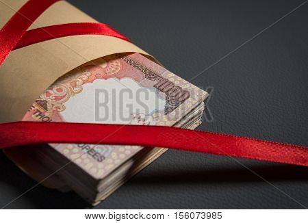 Demonetized One thousand Indian Rupee notes in a brown pocket, wrapped with red ribbon. A concept for bribe or illegal earning.