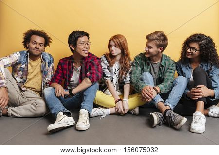 Multiethnic group of cheerful young friends smiling and talking together over yellow background