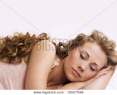 Sleeping beauty with long curly hair on light pink background